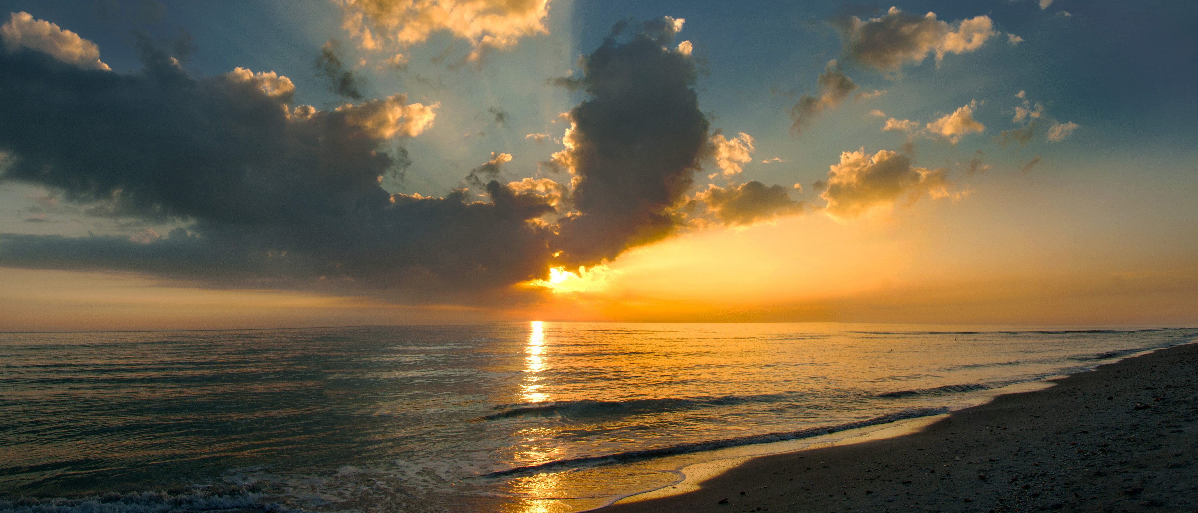 a serene sunset shines an orange and yellow light over the Atlantic Ocean