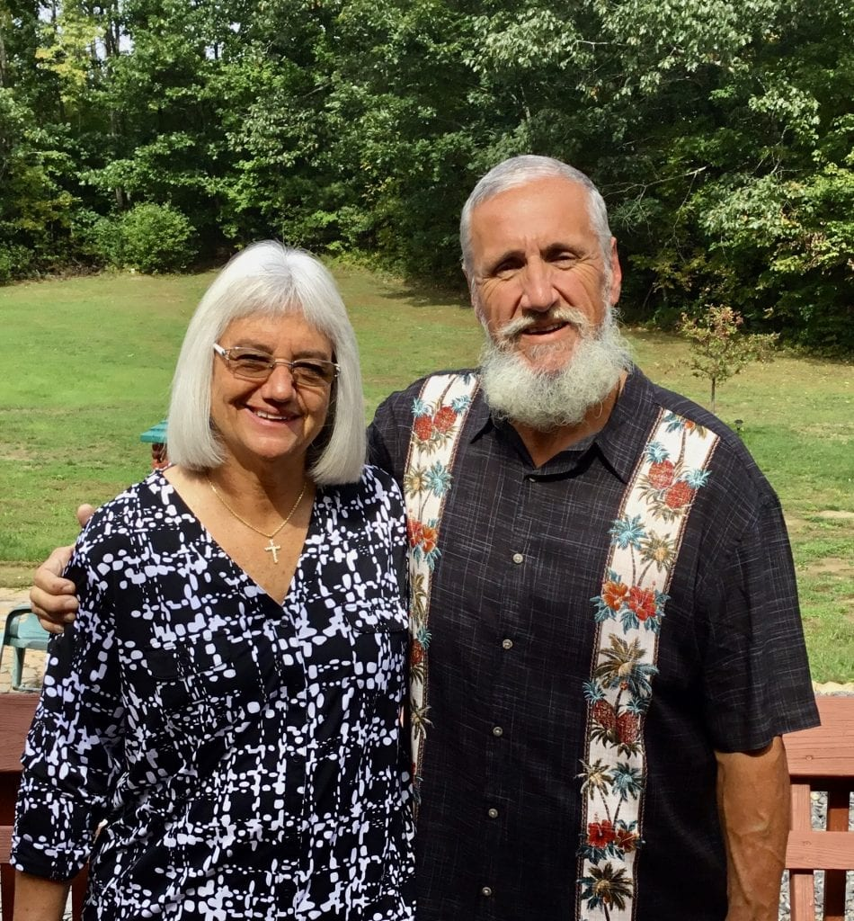Deb and her husband, Rolland, smile with a backdrop of green grass and pine trees.