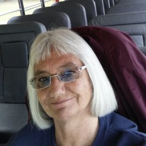 A stage 2 breast cancer survivor named Deb smiles while sitting on the school bus she drives as part of her job.