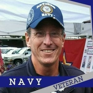 """A retired Navy Veteran and colon cancer survivor Daniel """"Dry Dock"""" Shockley smiles while wearing a blue Navy hat"""