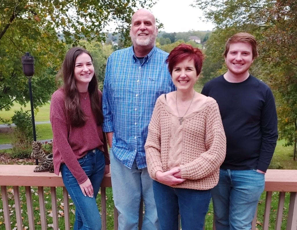 A pastor named Daniel Nicewonger lives with stage IV colon cancer smiles with his family, his wife, daughter and son.