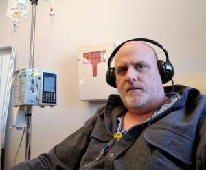 A pastor with stage IV colon cancer named Daniel Nicewonger listens to music while getting chemotherapy.
