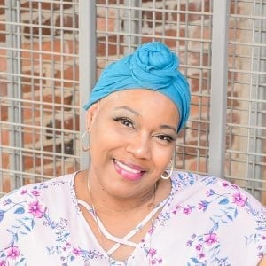 An African American breast cancer survivor named Felicia Robison smiles and radiates joy and positivity while wearing a teal head covering.
