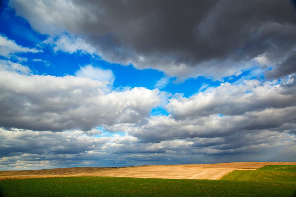 complicated-layers-of-clouds-hang-over-a-wheat-field